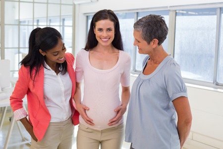 Attractive pregnant business woman at work smiling at the camera with her coworkers photo