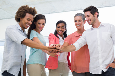 as one: Attractive business people joining hands in the workplace to unite as one Stock Photo