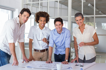 Team of architects smiling at camera in the office photo