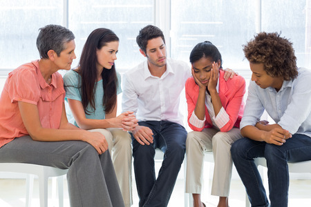therapy room: Group therapy in session sitting in a circle in a bright room Stock Photo