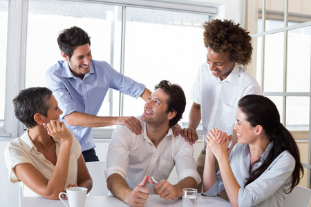 Attractive businessman praising coworker during a meeting