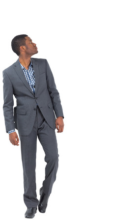 Serious businessman stepping ahead and looking up on white background photo