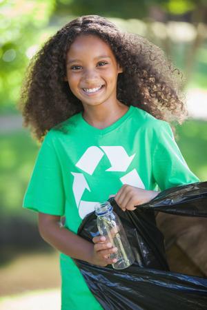 Young environmental activist smiling at the camera picking up trash on a sunny day