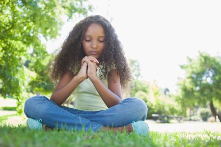 ni�o orando: Ni�a rezando en el parque en un d�a soleado