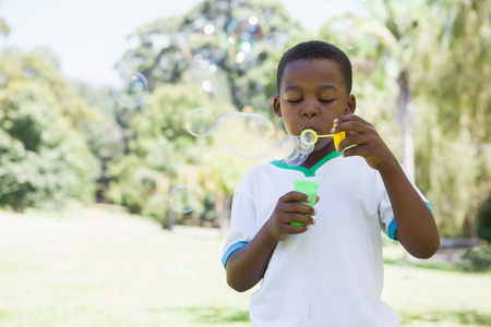 Little boy blowing bubbles in the park on a sunny day photo
