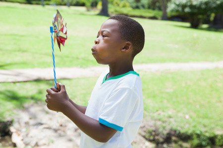 Little boy blowing pinwheel in the park on a sunny day photo