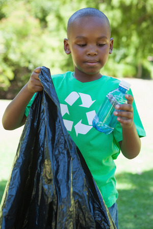 Little boy in recycling tshirt picking up trash on a sunny day photo
