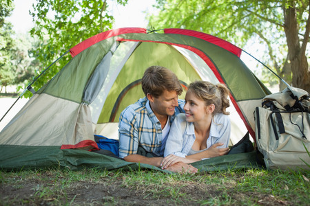 adventuring: Cute couple lying in their tent smiling at each other on a sunny day