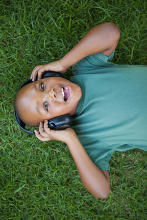 Little boy lying on grass listening to music smiling at camera on a sunny day photo