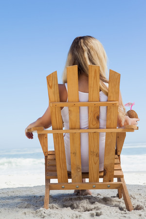 Pretty blonde sitting in deck chair holding coconut drink on a sunny day photo