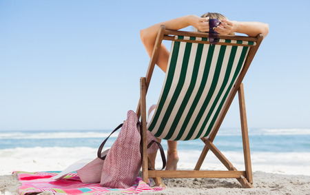 Woman sitting in deck chair at the beach with her beach bag and towel on a sunny day photo