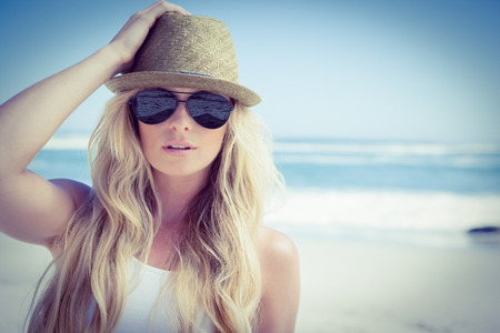 fair woman: Stylish blonde looking at camera on the beach on a sunny day Stock Photo