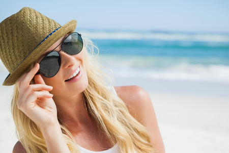 Stylish blonde smiling on the beach on a sunny day photo