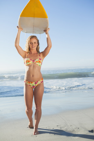 Gorgeous blonde surfer in bikini holding her board on a sunny day photo