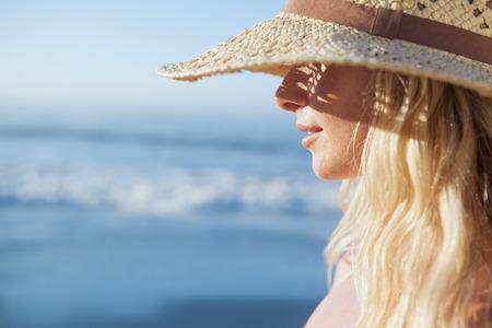 Prachtige blonde in strooien hoed lachend op het strand op een zonnige dag
