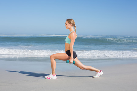 lunges: Fit woman doing weighted lunges on the beach on a sunny day