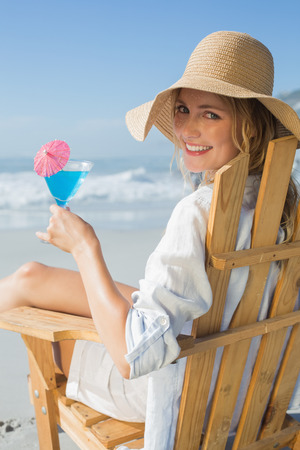 Smiling blonde relaxing in deck chair by the sea holding cocktail on a sunny day photo