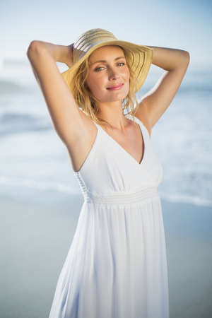maxi dress: Smiling blonde standing at the beach in white sundress and sunhat on a sunny day
