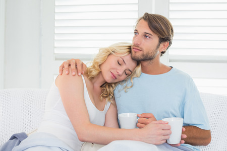 Smiling casual couple sitting on couch having coffee at home in the living room photo