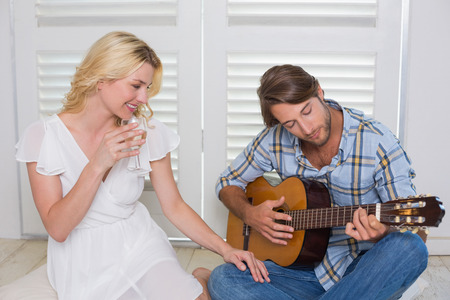 serenading: Handsome man serenading his girlfriend with guitar at home in the living room