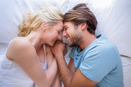 Cute couple relaxing on bed smiling at each other at home in the bedroom photo