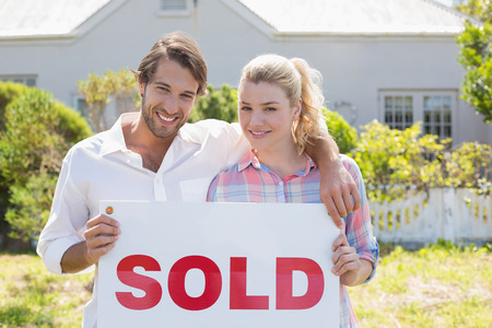 Cute couple standing together in their garden holding sold sign on a sunny day