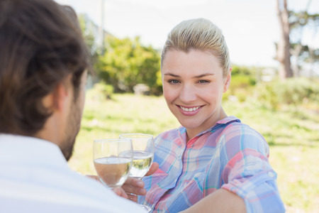 Happy young couple sitting in the garden enjoying wine together on a sunny day photo