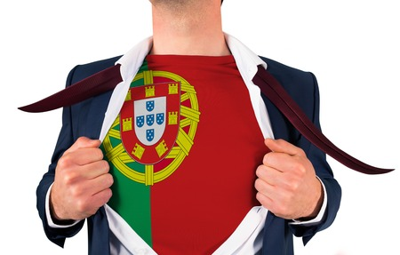 Businessman opening shirt to reveal portugal flag on white background photo