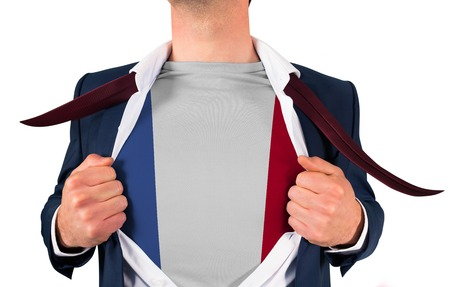 Businessman opening shirt to reveal france flag on white background photo