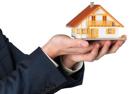 Businessman holding miniature house model on white background photo