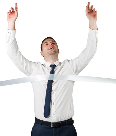 Smiling businessman crossing finishing line on white background photo