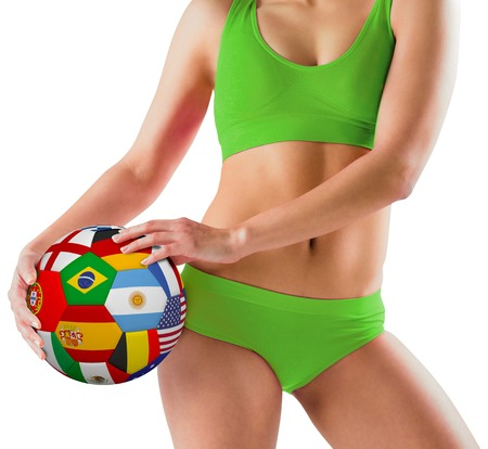 Fit girl in green bikini holding flag ball on white background photo