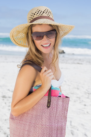 Beautiful laughing blonde on the beach holding bag on a sunny day photo