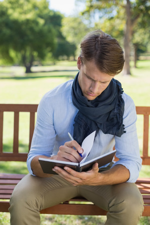 noting: Stylish young man writing in his notepad on park bench on a sunny day Stock Photo