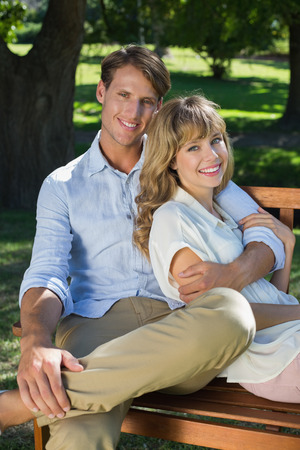 Affectionate couple relaxing on park bench together smiling at camera on a sunny day photo