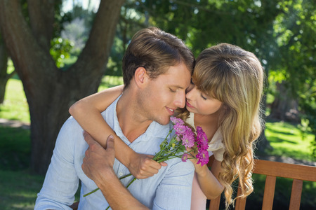 Cute couple embracing in the park with girl holding flowers on a sunny day photo