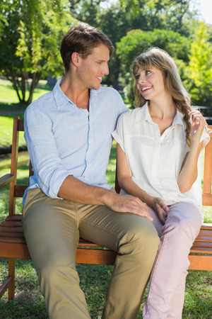 Cute couple sitting on park bench together chatting on a sunny day photo
