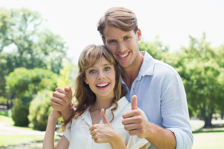 Attractive couple smiling at camera and showing thumbs up in the park on a sunny day photo