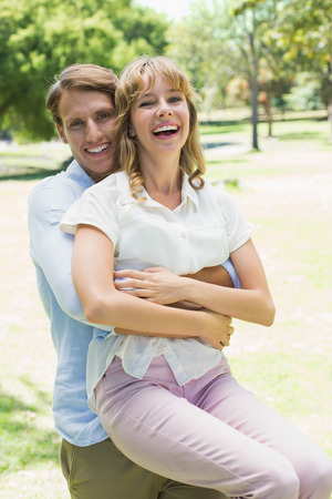 Handsome man picking up his laughing girlfriend in the park on a sunny day photo