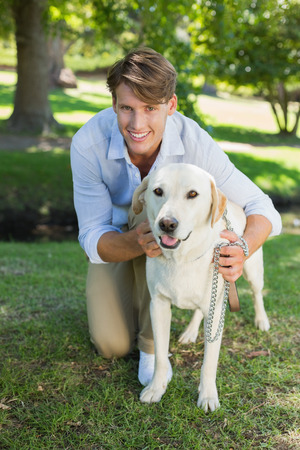 Handsome smiling man posing with his labrador in the park on a sunny day photo