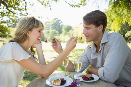 Cute couple feeding each other dessert on a sunny day photo