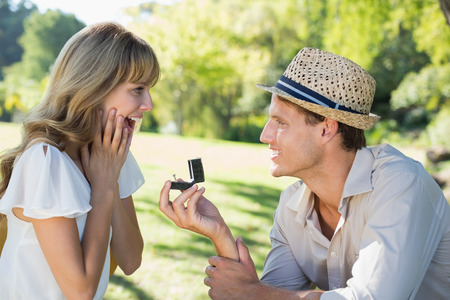engagement ring: Man surprising his girlfriend with a proposal in the park on a sunny day
