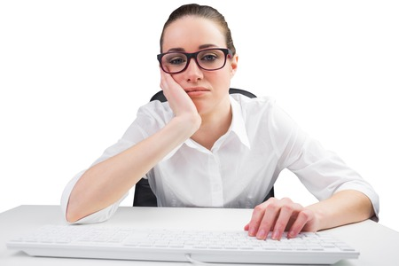 slumped: Businesswoman typing on a keyboard on white background