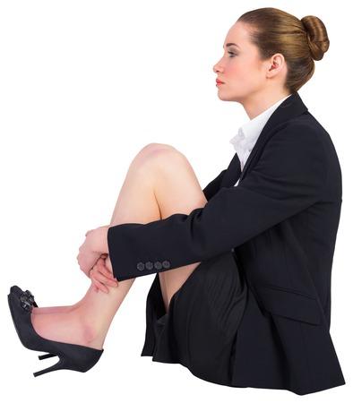 Pretty businesswoman sitting on floor on white background