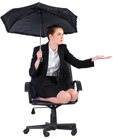 sheltering: Businesswoman holding a black umbrella on white background