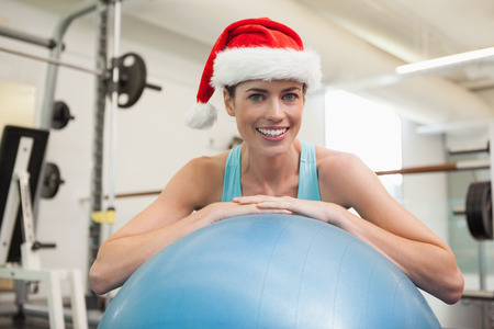 Fit smiling brunette in santa hat leaning on exercise ball at the gym photo