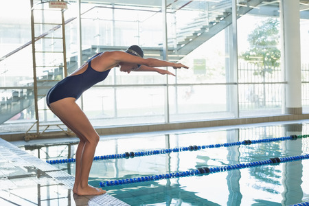 Fit swimmer about to dive into the pool at the leisure center photo