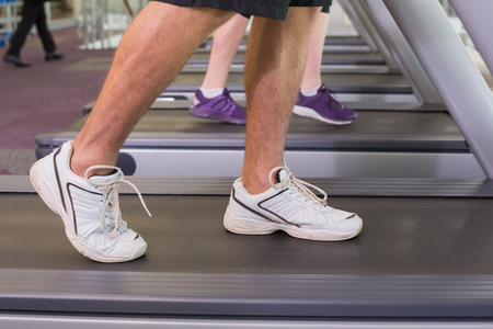 Man and woman walking on treadmills at the gym photo