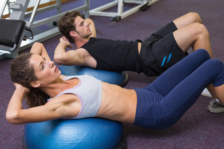 Fit man and woman doing sit ups on exercise ball at the gym photo
