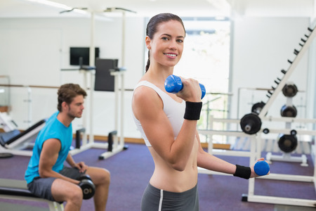 Fit brunette exercising with blue dumbbells smiling at camera at the gym photo